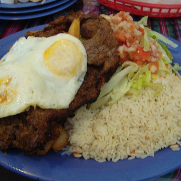 Bolivian Silpancho - Breaded Fried Beef Steak w/Fries, Rice, Letttuce & Fried Eggs topped with tomato/onion pico de gallo  @ La Chocita Grill