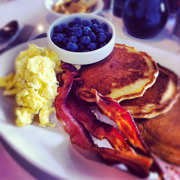Pancakes with a side of blueberries and bacon @ Over Easy