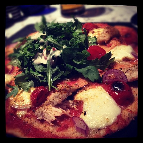 Polla ad Astra Leggera pizza. Pizza with thinner, crispier Romana dough, under 500 calories and with hole in middle for salad. Toppings are chicken, mozzarella, sweet peppadew peppers, Cajun spices, red onions. Tasted really good :) @ Pizza Express