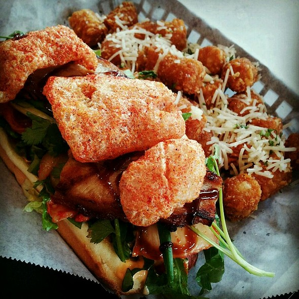 Chicharron Dog with beef hot dog, pork belly, kimchi, cilantro, spicy aioli and spicy chicharron and Parmesan, truffle and garlic tater tots @ The Slaw Dogs