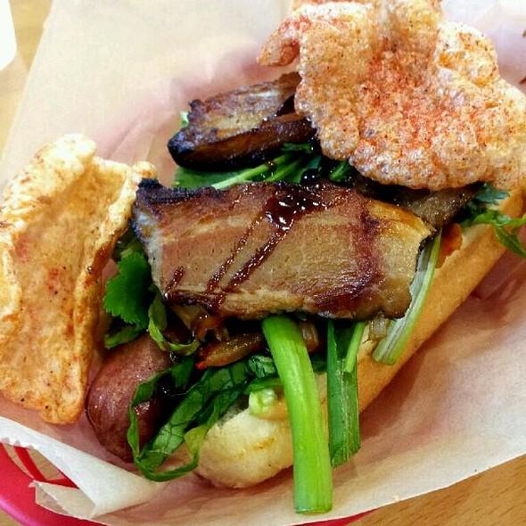 Chicharron Dog with beef hot dog, pork belly, kimchi, cilantro, spicy aioli and spicy chicharron @ The Slaw Dogs