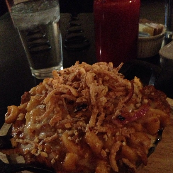 BBQ Mac -pulled pork, red onion, BBQ cheese sauce,  cheddar, Swiss & topped with fried onion strings & a  rib @ Our House Bistro