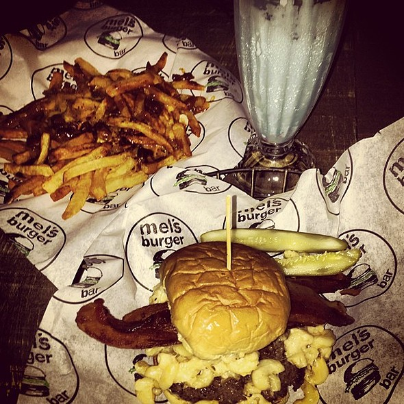 Entire week at the gym -- gone in one sitting -- the widowmaker is a burger which contains not only bacon but Mac and cheese. And yup that's a chili cheese fries accompanying it. And that blue concoction? That's called Stumbles the Clown which is cotton c @ Mel's Burger Bar