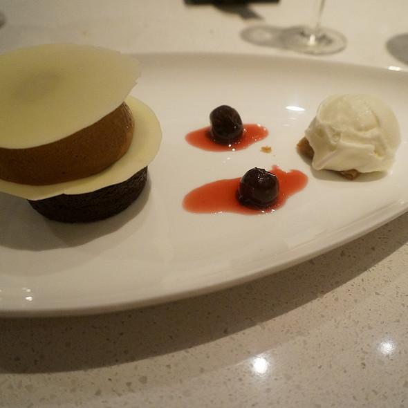 Trois chocolate, bittersweet dense cake, milk mousse, white chocolate amaretto gelato, semi cooked black cherry