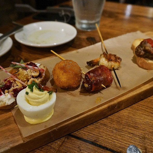 Spanish food tapas, pintxos, bacon-wrapped shrimp, chorizo-wrapped date, goat cheese croqueta with lemon gastrique, short-rib stuffed piquillo pepper, deviled egg, bacon, mustard, and roasted beet crostini, herbed goat cheese and hazelnuts
