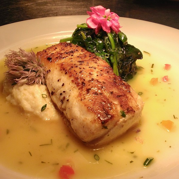 Pan seared blue nose bass served over grits and sauteéd spinach topped with a banana rosemary buerre blanc - ECHO St.Simons Island, Saint Simons, GA