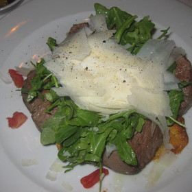 Sliced beef tenderloin over thin potato tart with arugula, shaved parmesan and truffle oil