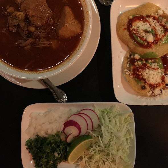 Pozole – Pork And Hominy Stew Served With Tortillas,  Shredded Cabbage, Onion And Cilantro Garnish.