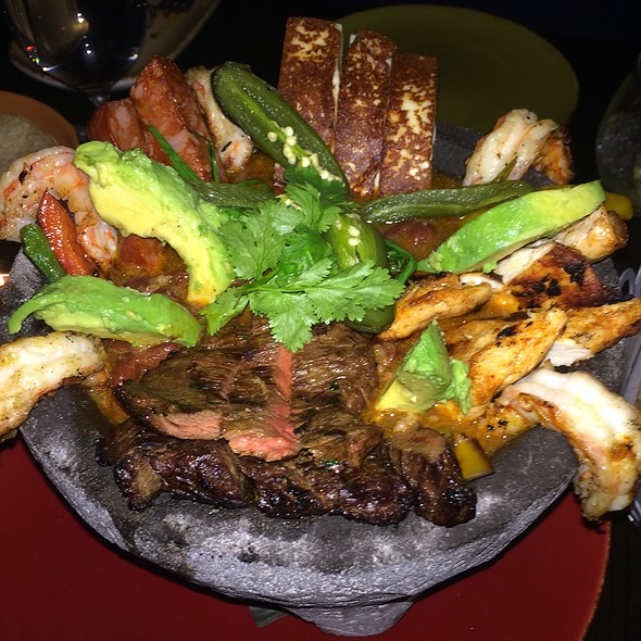 """Family Style """"Molcajete"""", Grilled Skirt Steak, Chicken, Shrimp, Chorizo, Peppers, Queso Fresco Served Over Smokey Black beans, Garnished with Avocado, Salsa Verde and Chicharrones Served with Warm Tortillas @ Cocina Lolo"""