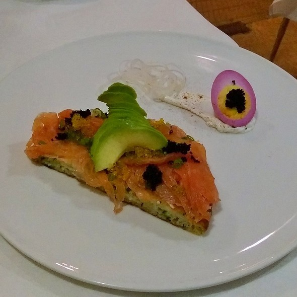 Smoked salmon on a savory pancake with roe, avocado, passed egg, and labneh