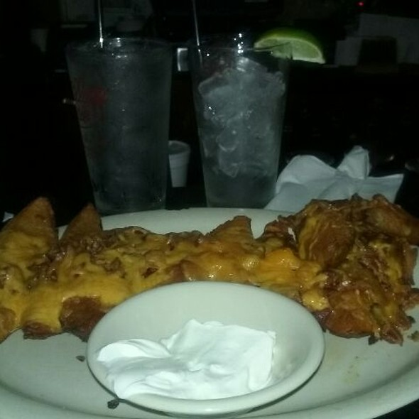 Potato skins – Scooped out potatoes, seasoned, fried and baked with cheddar and bacon side of sour cream @ The Village Cafe