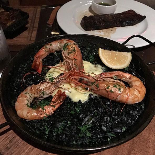 Paella negra – black rice squid ink paella with lobster, scallops, calamari, clams, mussels, prawns with artichoke, tomato salad and saffron aioli toast