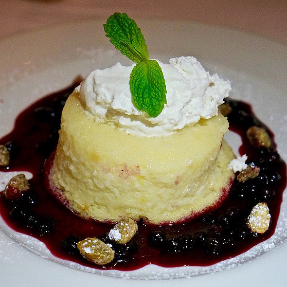 Lemon buttermilk soufflé cake, fresh huckleberry sauce, candied pistachios