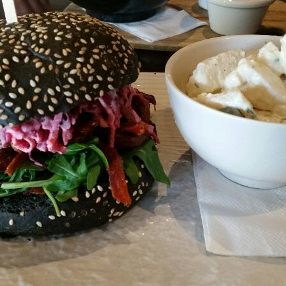 Pulled Brisket Burger With Pickled Beetroot Slaw, Aioli, Tomato Relush And Rocket On A Charcoal Bun With Potato Salad
