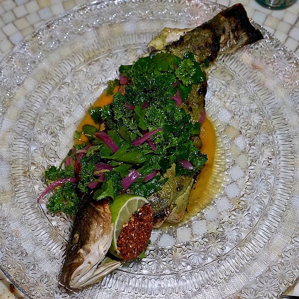 Whole branzino Mediterranean sea bass, green harissa, pickled mango chutney, pickled red onions, herb salad