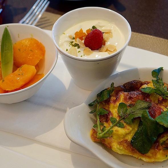 Soho breakfast Greek yogurt, almond slivers, apricots, papaya-mango salad, omelette with asparagus, watercress–