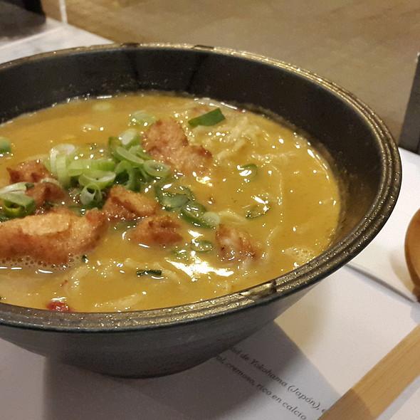 Ramen de curry con fideos de arroz, coco y topping pollo