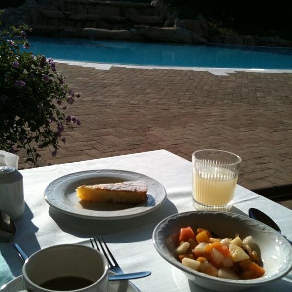 Colazione con macedonia fresca, torta, caffè e spremuta di pompelmo
