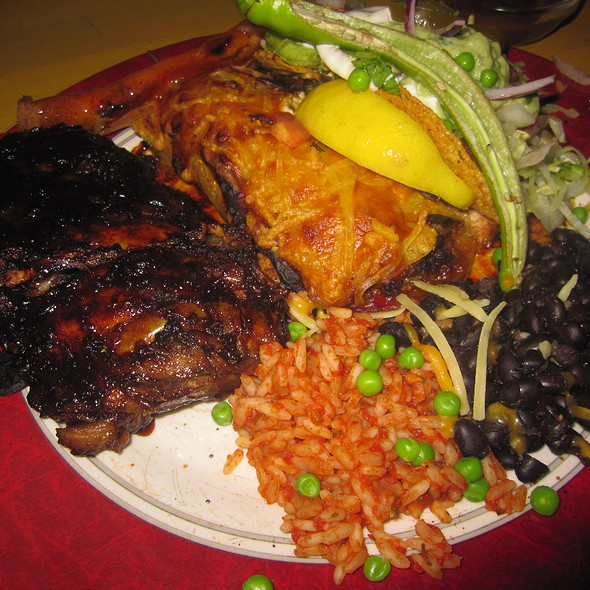Enchilada with beef, Taco with Salmon, Taquito with guajillo sauce, Spareribs, Salad with sour cream, salsa mexicana, rice and beans. @ Mexicaans Restaurant El Popo