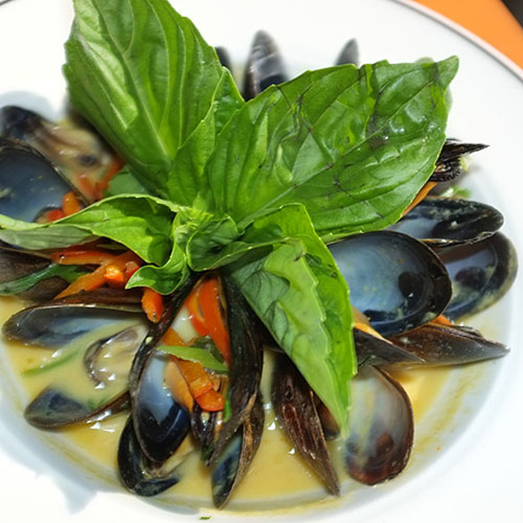 Mussels in Thai Coconut-Curry The mussels are simmered in Thai red curry-coconut broth finished with sweet red peppers and scallions, garnished with lime and basil. - Salty's at Redondo Beach, Des Moines, WA